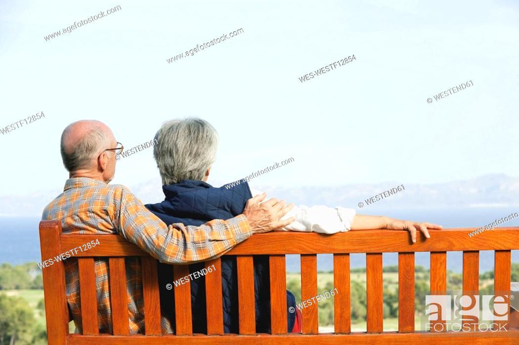 Stock Photo: Spain, Mallorca, Senior couple sitting on bench, rear view.