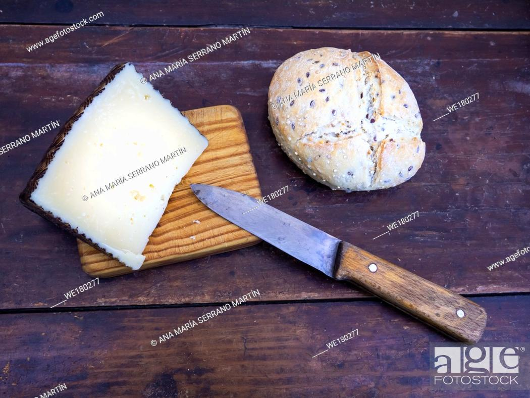 Stock Photo: A wedge of cheese on a wooden board with an antique knife and rustic spanish bread.