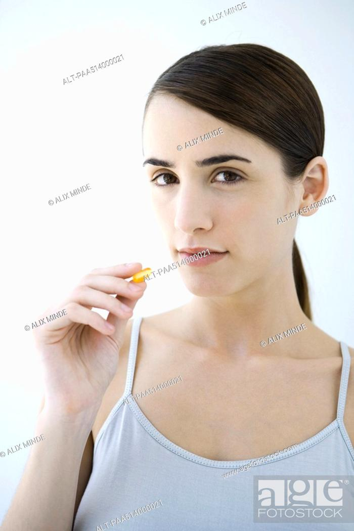 Stock Photo: Woman holding up medicine capsule, looking at camera.