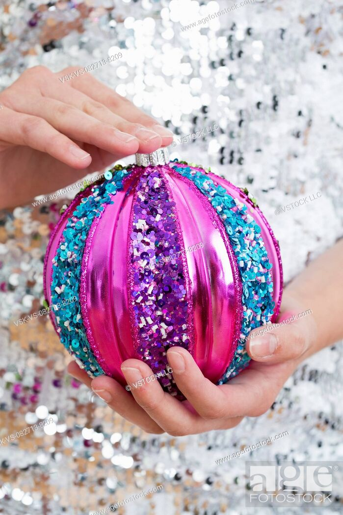 Imagen: Mid section of teenage girl (14-15) holding Christmas ornament.