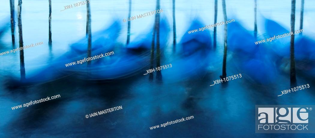 Stock Photo: Moored gondolas moving under waves with long exposure on Grand Canal in Venice Italy.