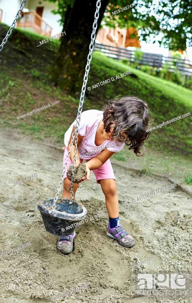 Stock Photo: A four years old caucasian girl playing with sand in a playground.