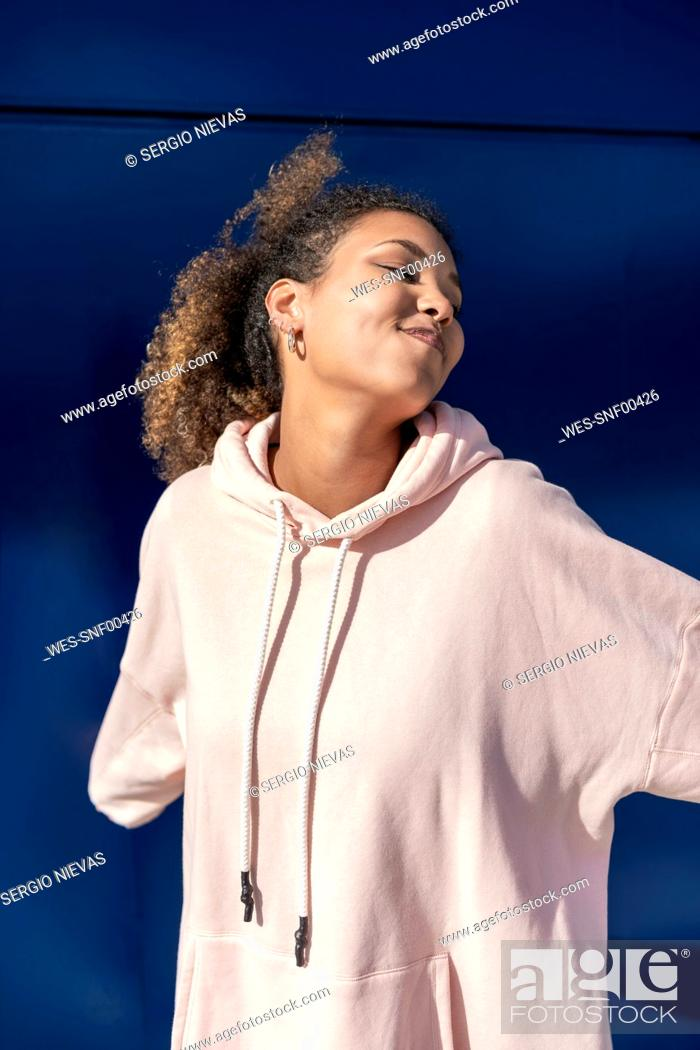 Stock Photo: Smiling young woman wearing pink hoodie sweater in front of blue wall.
