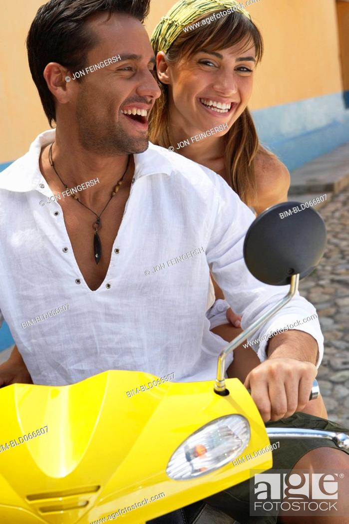 Stock Photo: Couple riding scooter.