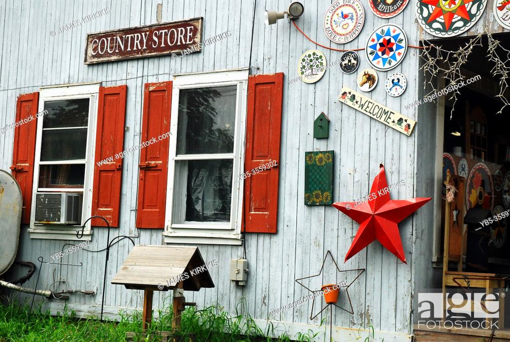 Stock Photo: Amish Hex signs and other antiques hang on the exterior wall of a country store in Reading, Pennsylvania.