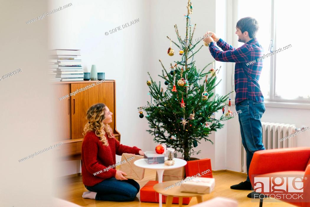 Stock Photo: Couple decorating Christmas tree at home.