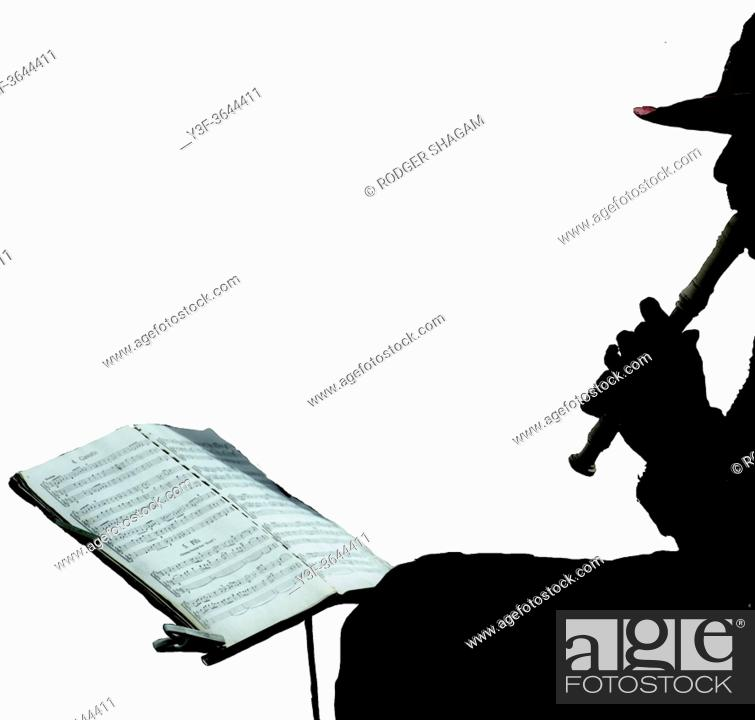 Photo de stock: Music busker playing a recorder and following the sheet music on a music stand.