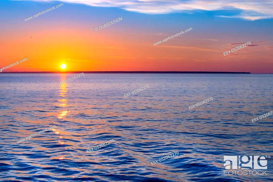 Stock Photo: Sunset over sea horizon. Bright sun is reflected from water surface, evening sky with sparse Cirrus clouds. Sea Nordic walk on passenger ferry from Helsinki to.