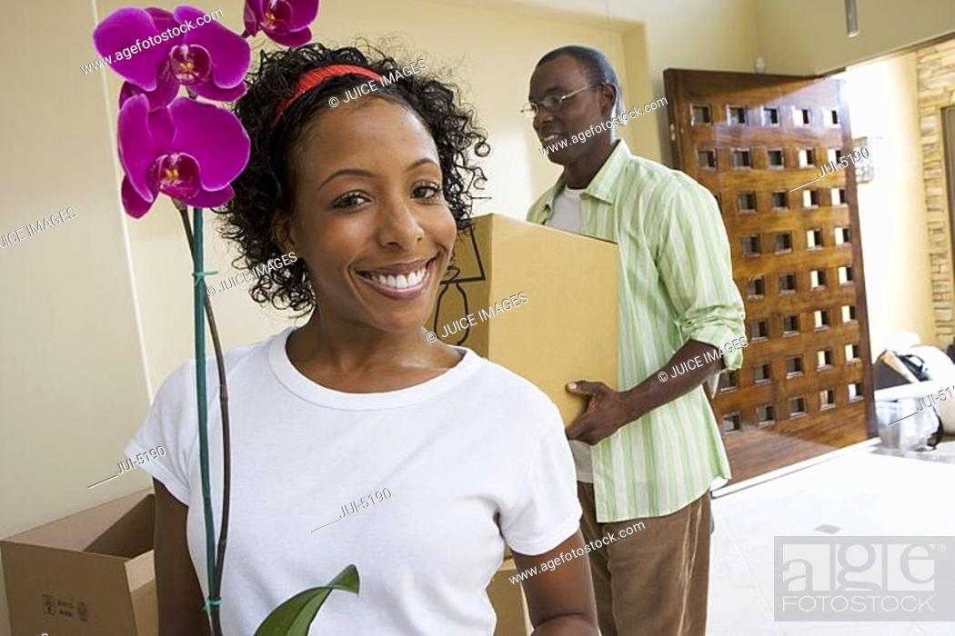 Stock Photo: Couple moving house, man carrying box in hallway, woman holding pot plant, smiling, portrait.