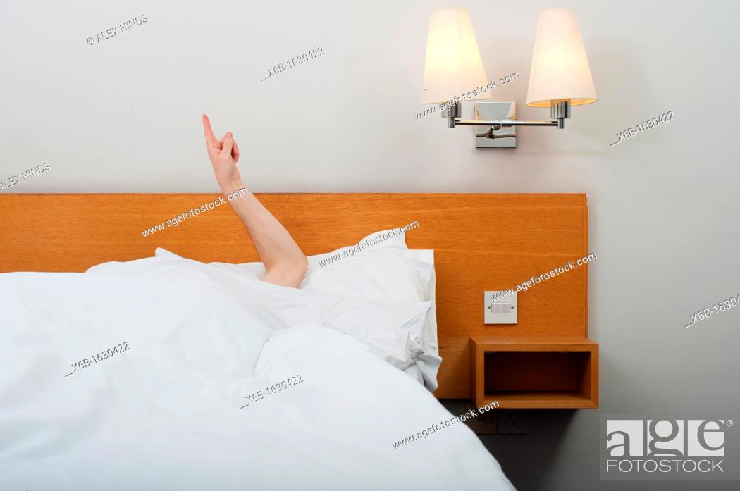 Stock Photo: Arm pointing up from under bed covers.