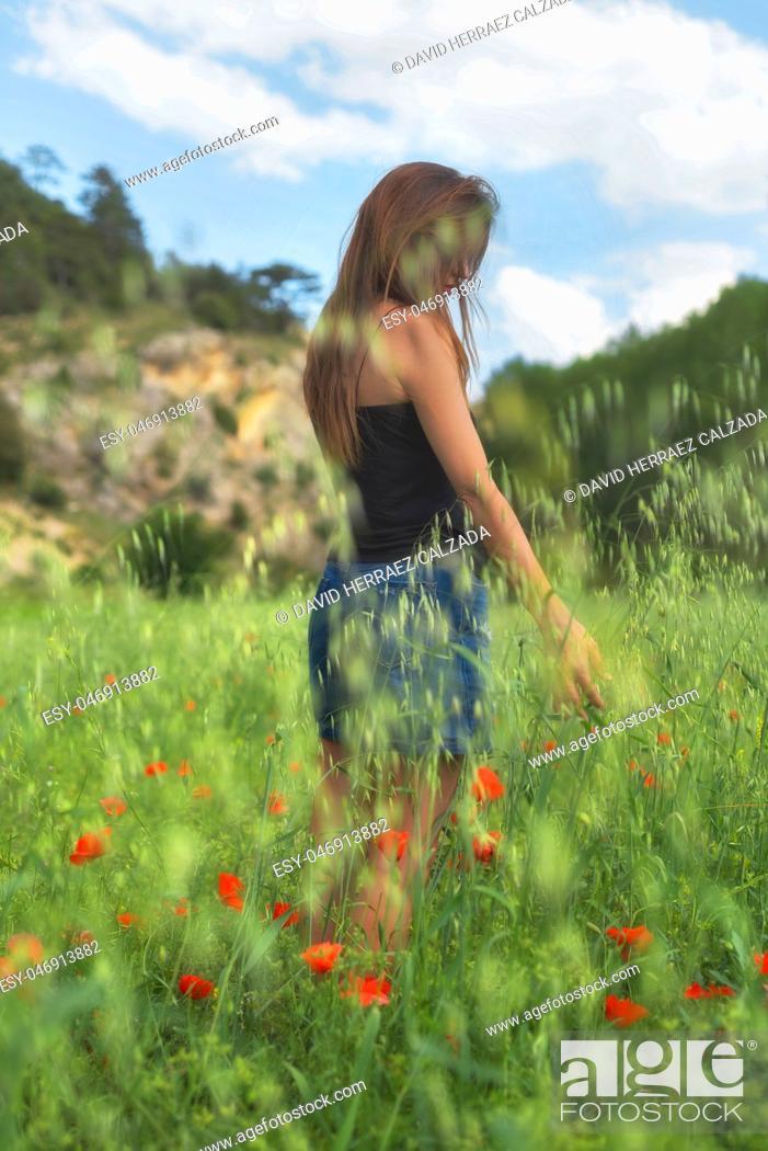 Imagen: Woman enjoying a walk in a poppy field under the summer sun.