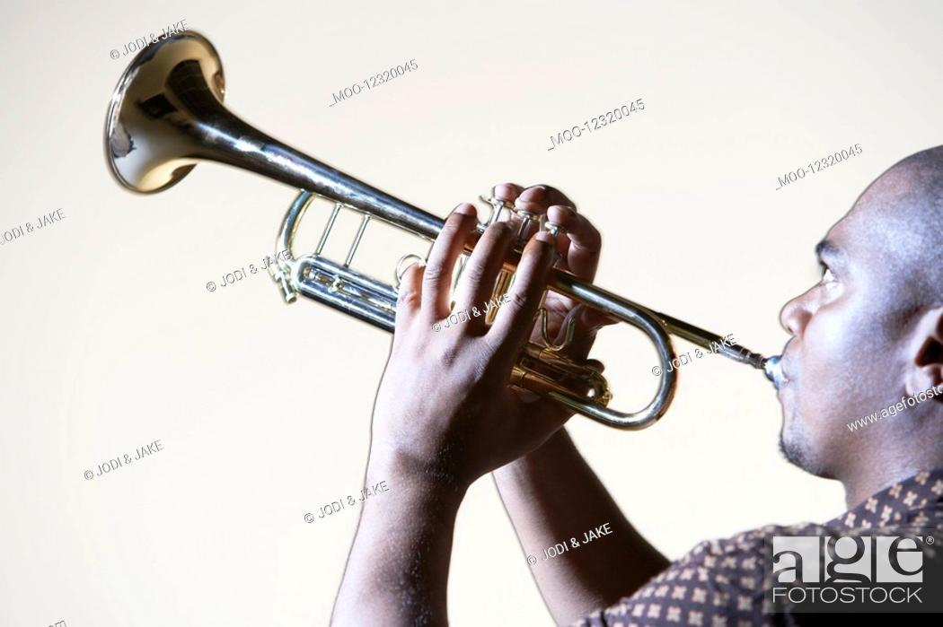 Stock Photo: Trumpeter playing looking up close-up side view.