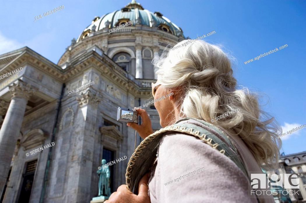 Stock Photo: Woman taking picture of church.