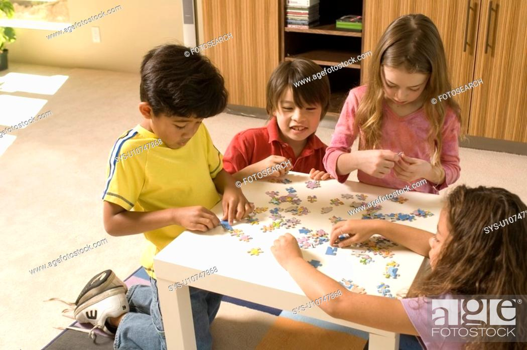 Stock Photo: Portrait of kids playing a puzzle.