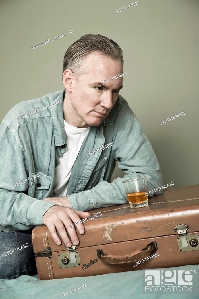 Stock Photo: Middle-age man with a drink setting on a suitcase.