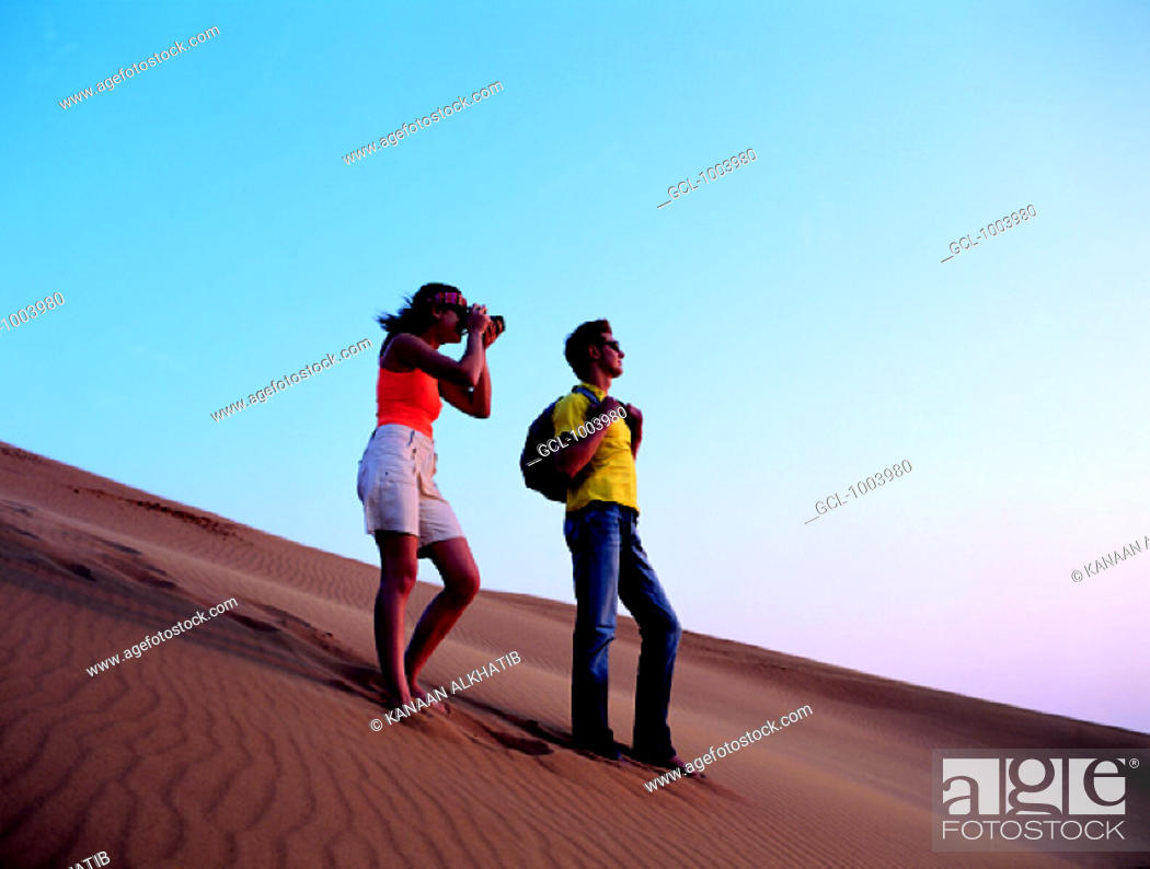 Stock Photo: Western tourist taking pictures in the desert of the United Arab Emirates.