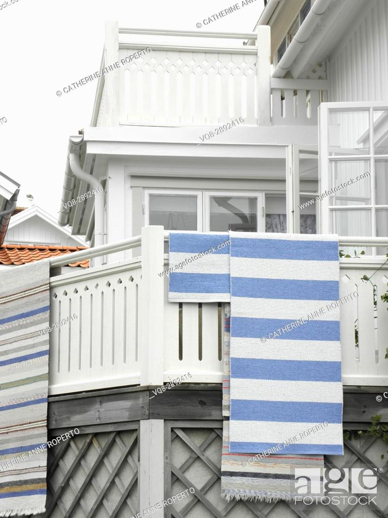 Imagen: Stripy woven mats hanging out to dry after the rain on the wooden balcony of a harbour side house near Gothenburg, Sweden.