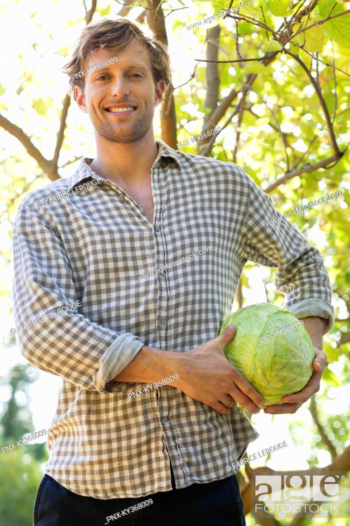 Stock Photo: Portrait of a man holding a cabbage.