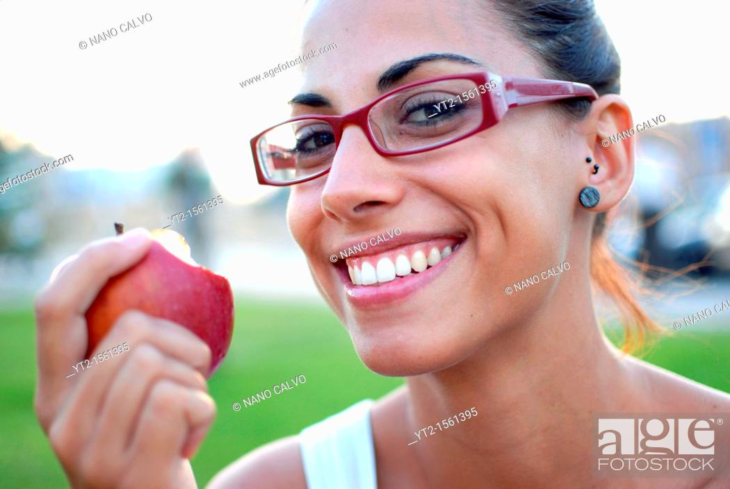 Stock Photo: Young woman eating a red apple in nature.
