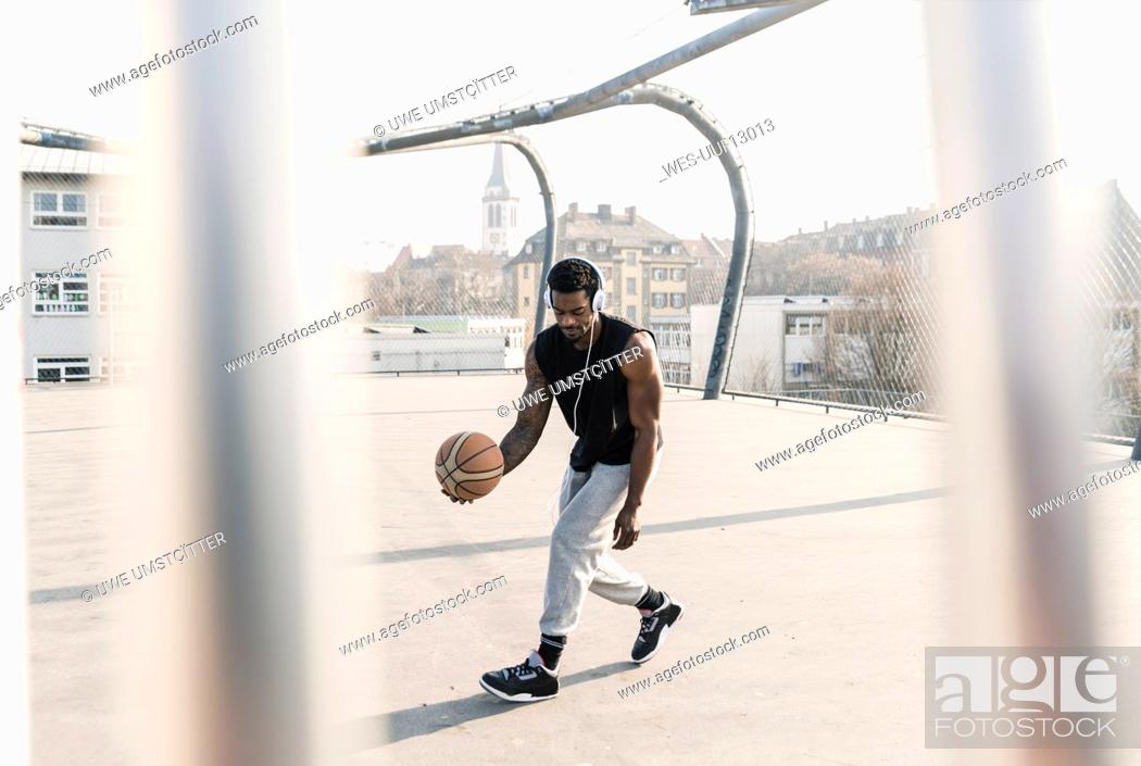 Stock Photo: Basketball player with headphones in action on court.
