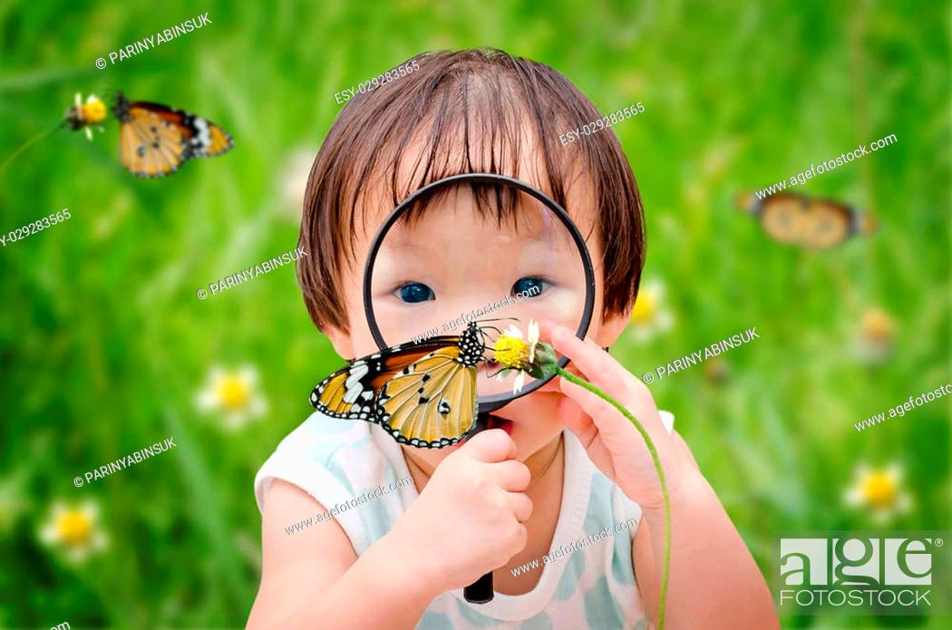 Stock Photo: little asian girl with magnifying glass outdoors in the day time.