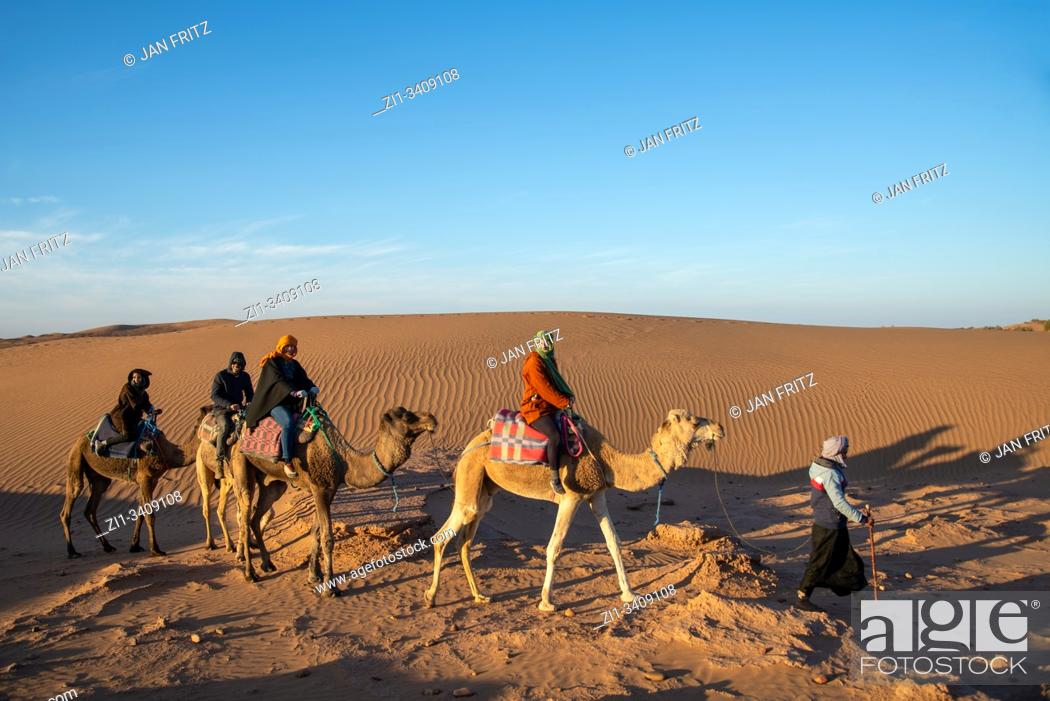 Imagen: tourists riding camels in desert of Morocco.