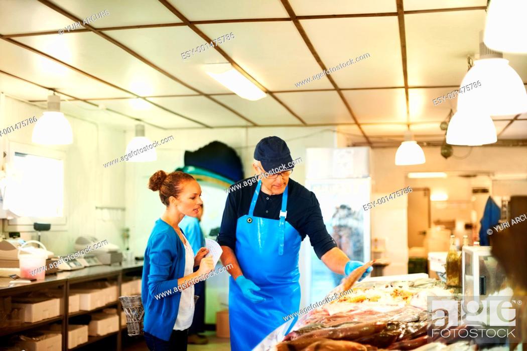 Photo de stock: Fishmonger showing fish to a young woman.