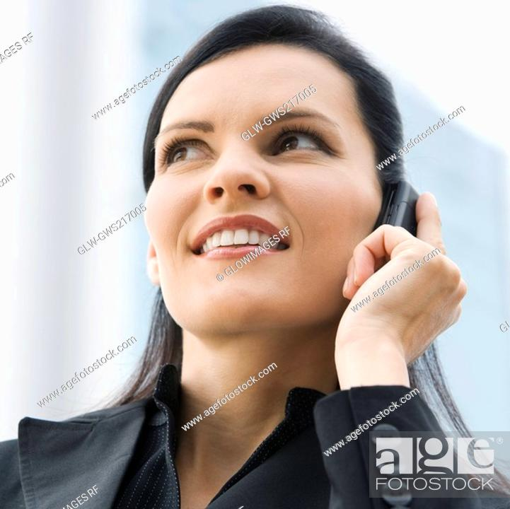 Stock Photo: Close-up of a businesswoman talking on a mobile phone and smiling.