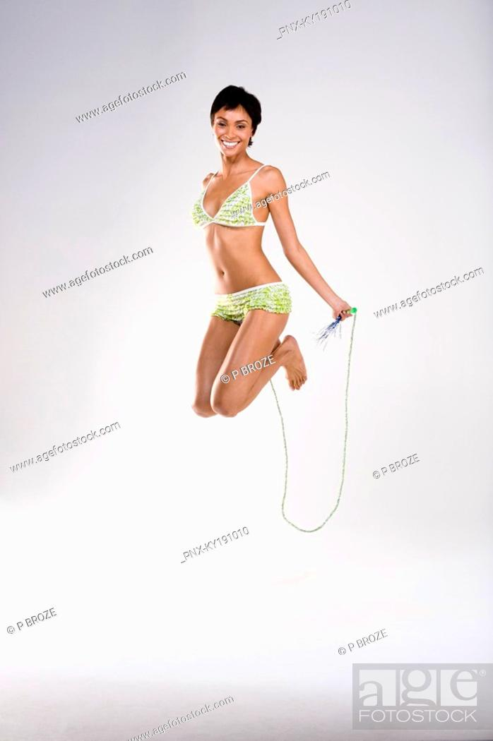 Stock Photo: Portrait of a woman skipping with a rope.