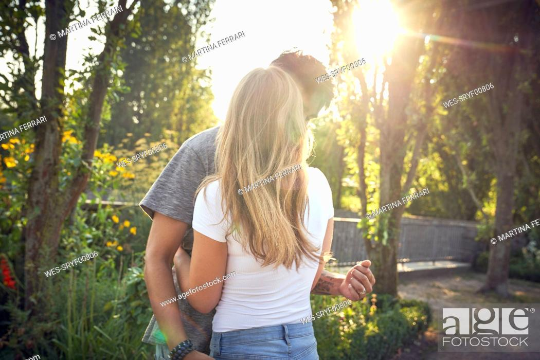 Stock Photo: Happy young couple embracing and kissing in a park in summer.