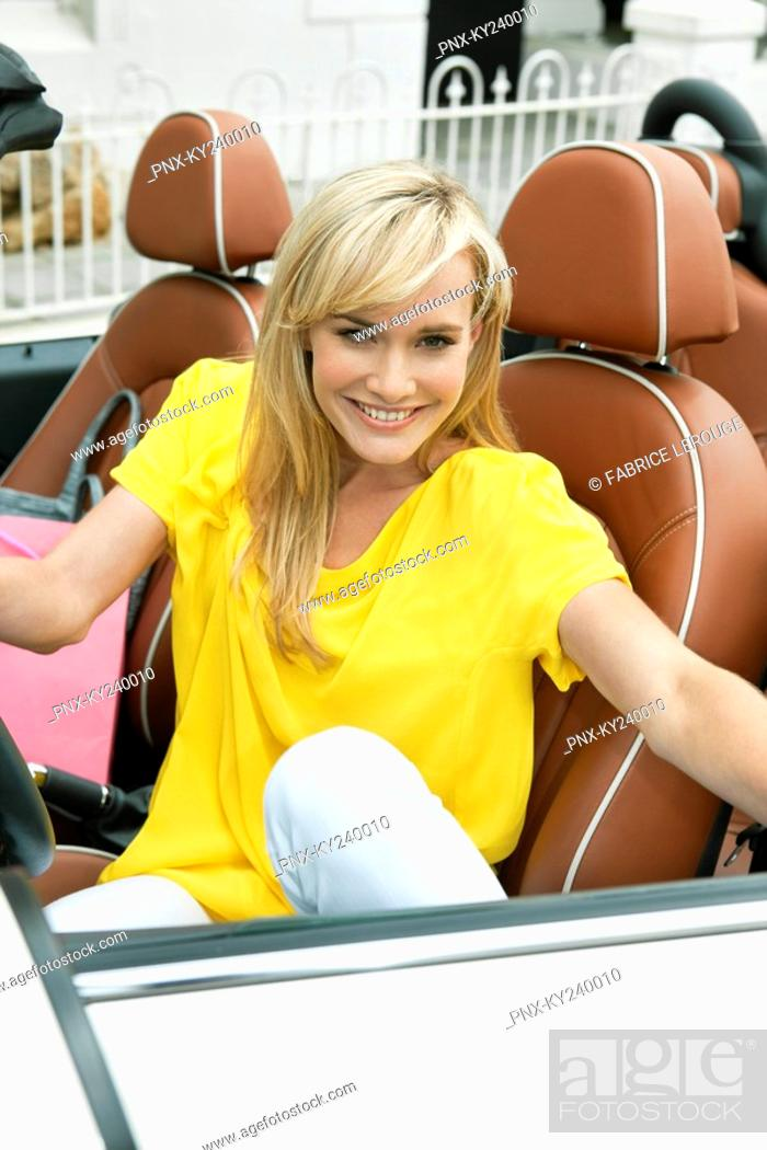 Stock Photo: Woman sitting in a car and smiling.