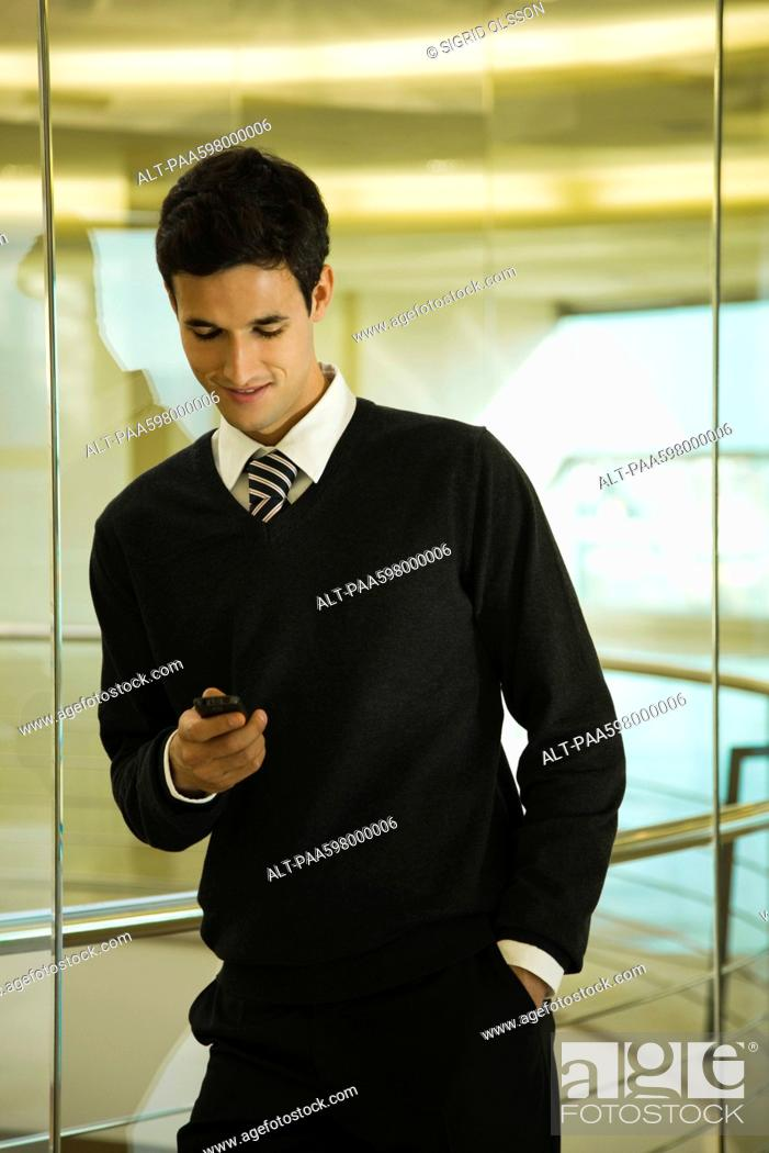 Stock Photo: Businessman text messaging with cell phone.