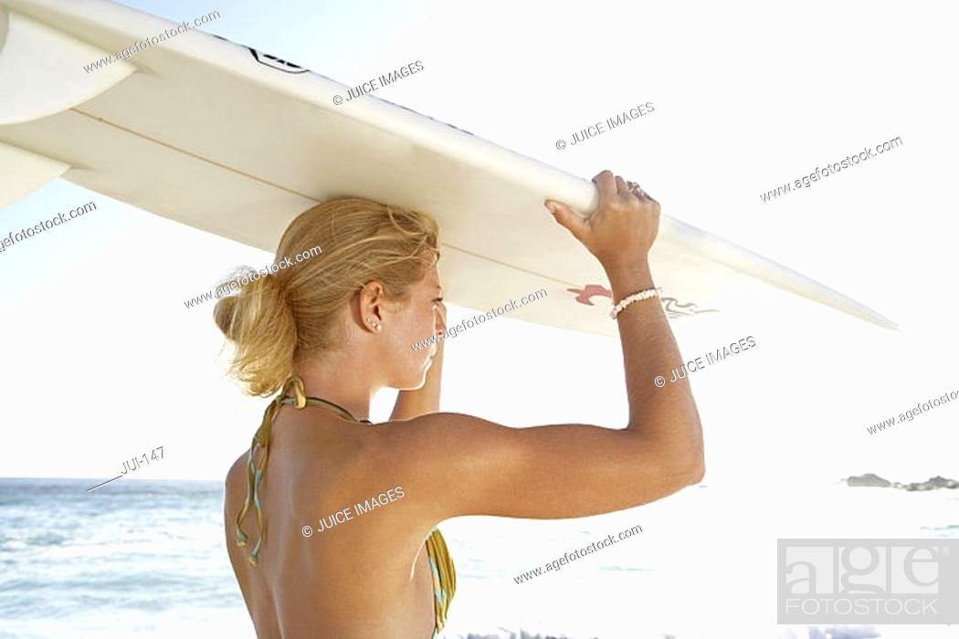Stock Photo: Young woman standing on beach in bright sunlight, carrying surfboard on head, side view.