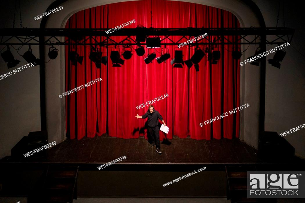 Stock Photo: Rehearsing actor with script standing on theatre stage in front of red curtain.