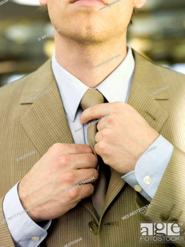 Stock Photo: Young businessman adjusting tie, mid section, close-up.
