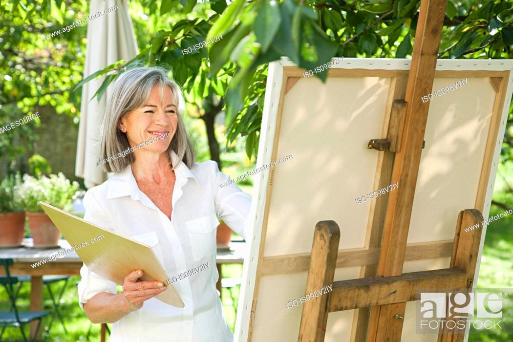 Stock Photo: Mature woman painting at easel.