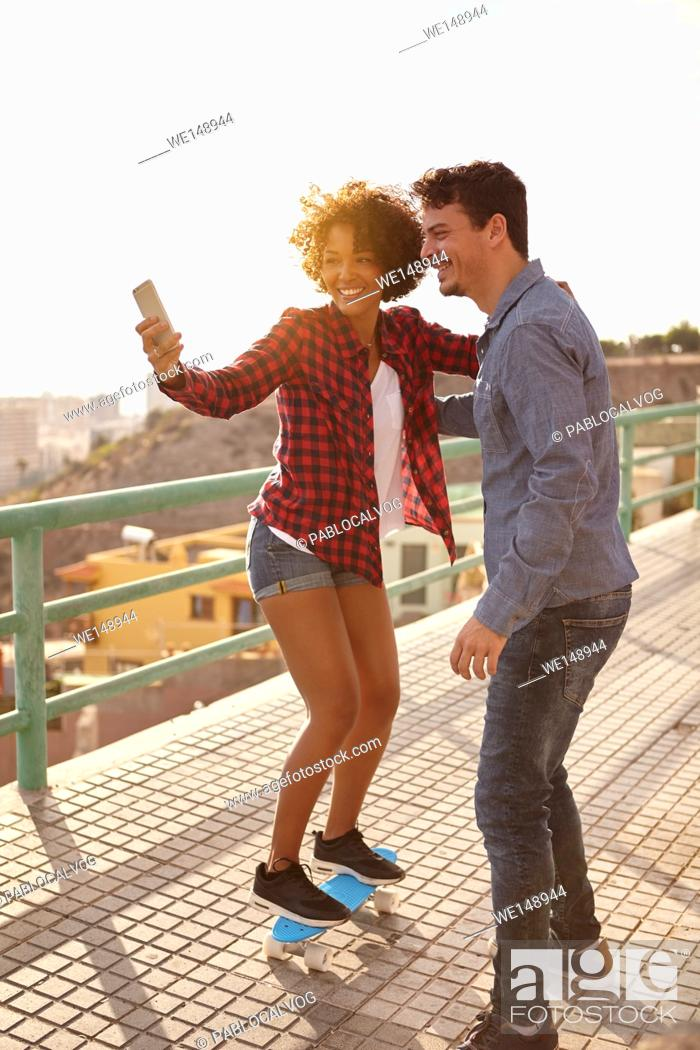 Stock Photo: Curly haired girl posing on a skateboard while boy holds her to take a selfie of them with big toothy smiles.