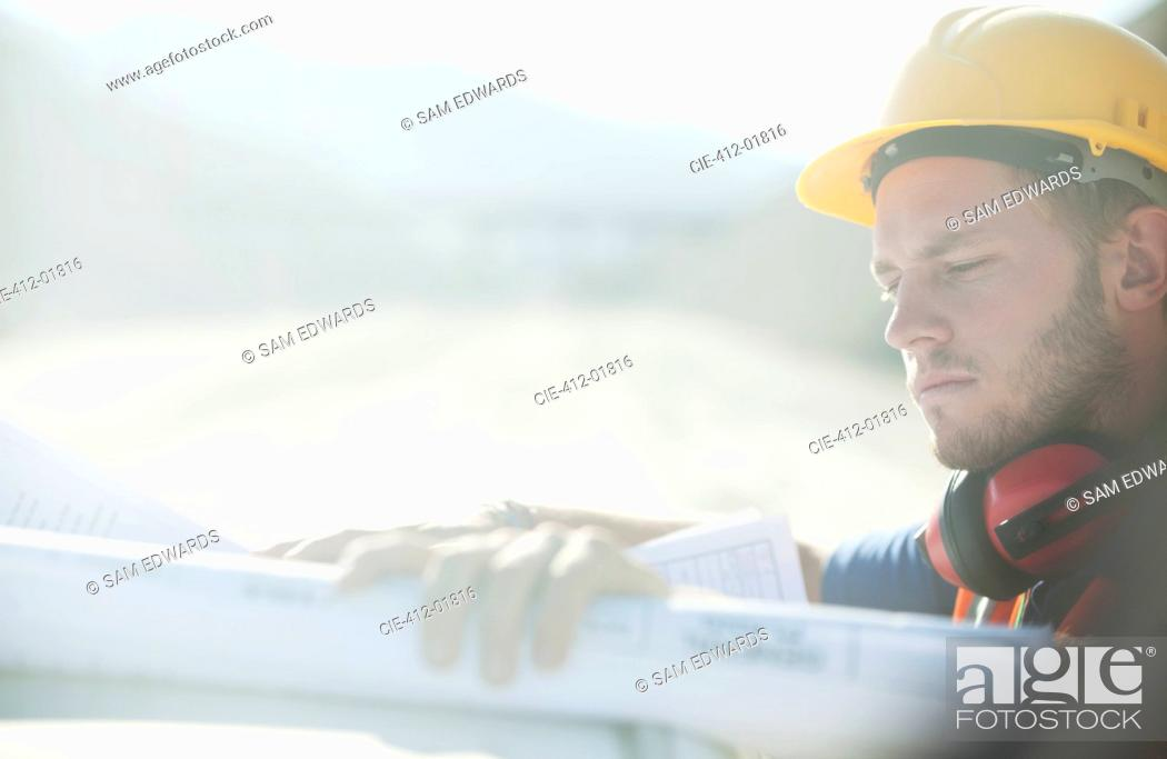 Stock Photo: Worker reading blueprints on site.