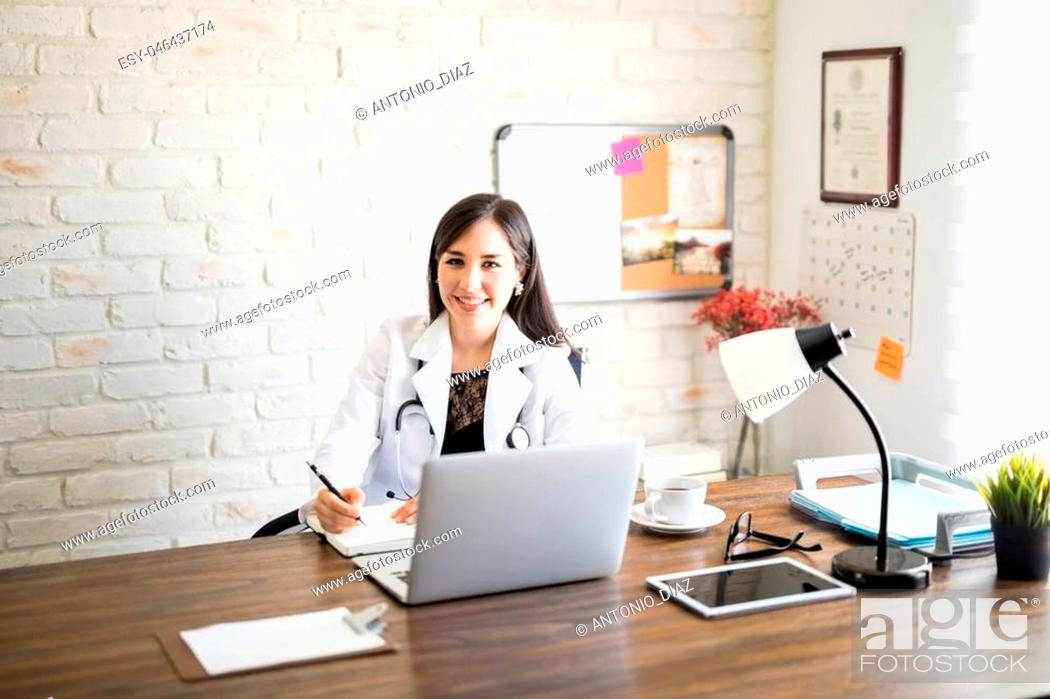 Imagen: Portrait of pretty hispanic female medical professional sitting at her desk looking at camera and smiling while making notes.