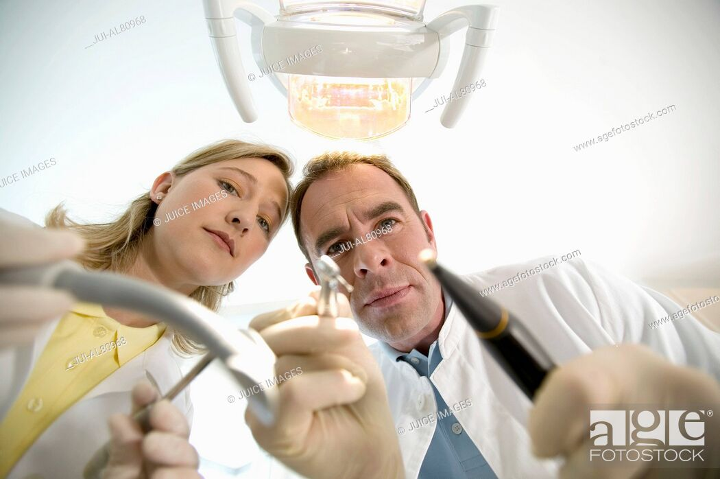 Stock Photo: Dentist and dental assistant holding dental tools.