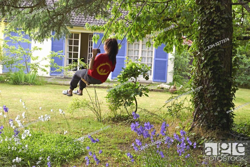Imagen: young girl on a swing, Eure-et-Loir department, Centre-Val de Loire region, France, Europe.