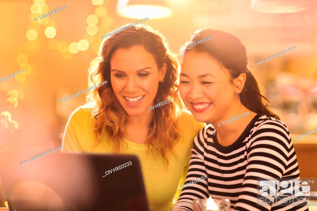 Stock Photo: Smiling women friends using laptop.