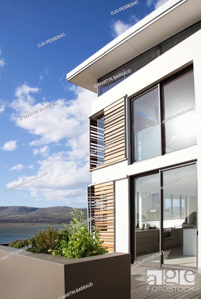 Stock Photo: Sun shining on window of modern house overlooking lake.
