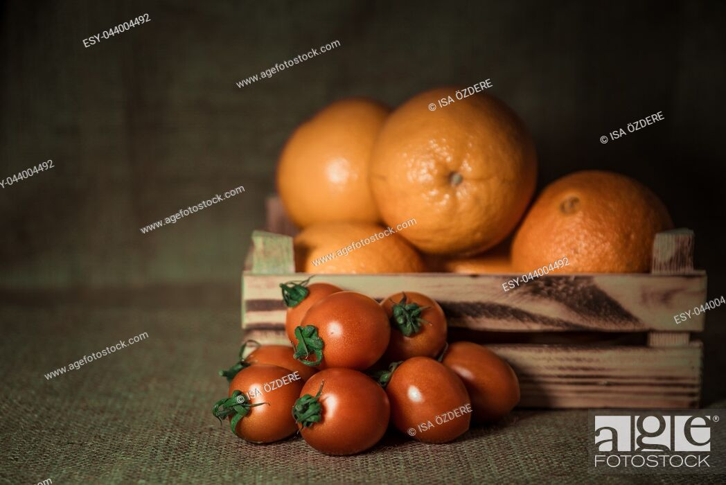 Imagen: Oranges in crate and cherry tomatoes together on rustic sackcloth background.