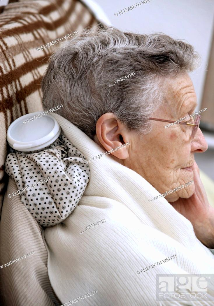 Stock Photo: Elderly woman using a hot water bottle for neck and shoulder pain.