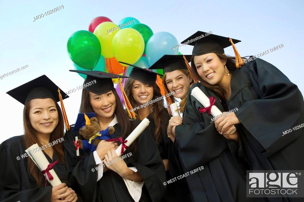 Stock Photo: Group of graduates with diplomas and balloons outside portrait.