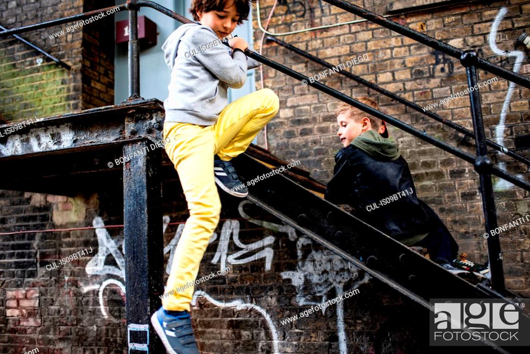 Stock Photo: Boys playing on metal staircase.