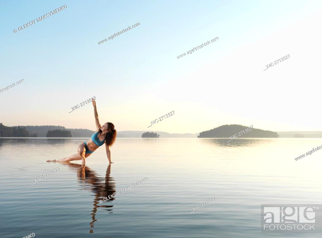 Photo de stock: Young woman practicing Hatha yoga on a floating platform in water on the lake in early morning. Yoga, a variation of Triangle pose, Trikonasana.