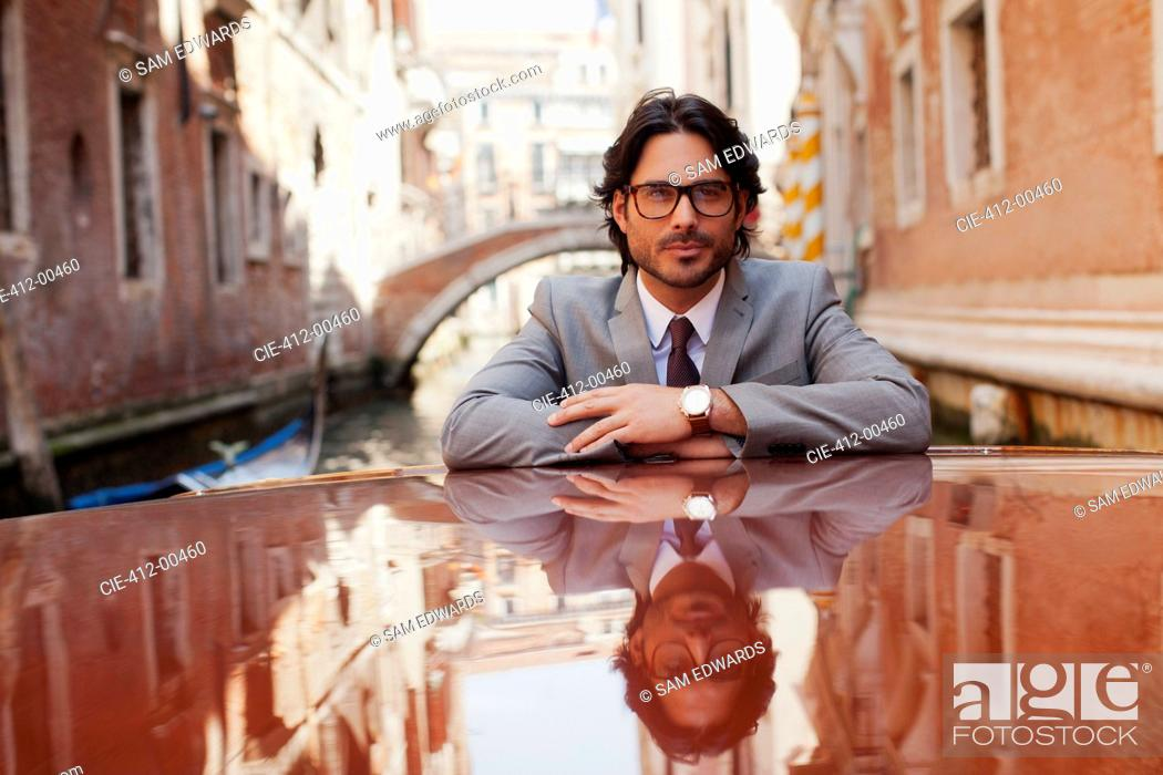Stock Photo: Portrait of serious businessman riding boat in canal in Venice.