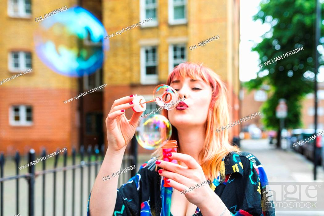 Stock Photo: Young woman with dip dyed hair blowing bubbles.